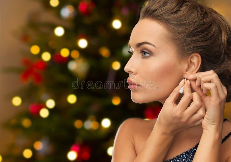 Mujer hermosa con el pendiente del diamante en la Navidad foto de archivo libre de regalías