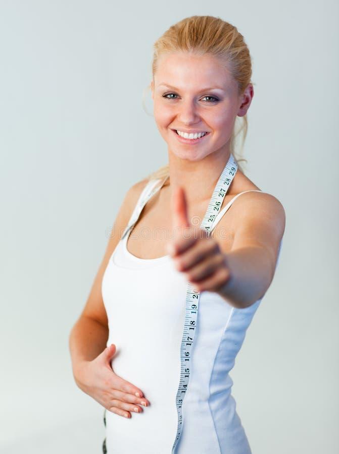 Mujer hermosa con el pulgar para arriba después de la pérdida de peso imágenes de archivo libres de regalías