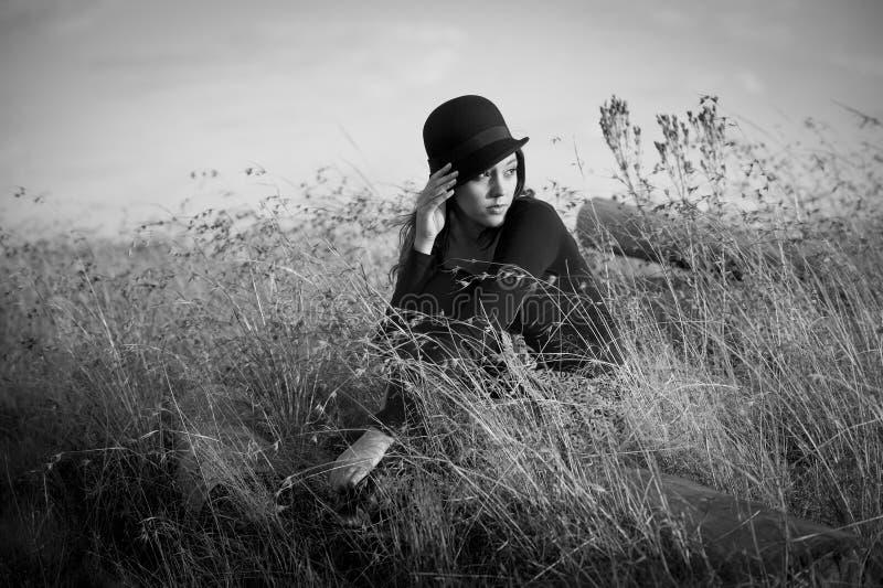 Mujer hermosa con el sombrero asentado en campo imagen de archivo