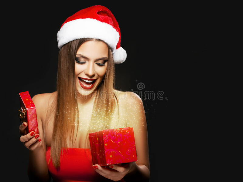 Mujer hermosa con el sombrero del ` s de Papá Noel que abre un presente imagenes de archivo