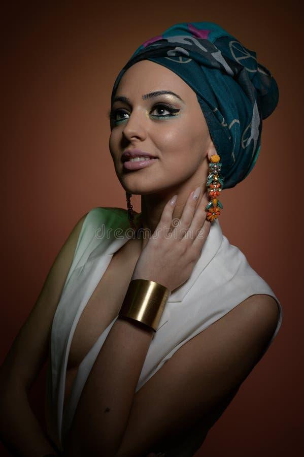 Mujer hermosa con el turbante Hembra atractiva joven con el turbante y los accesorios de oro Mujer de moda de la belleza fotografía de archivo libre de regalías