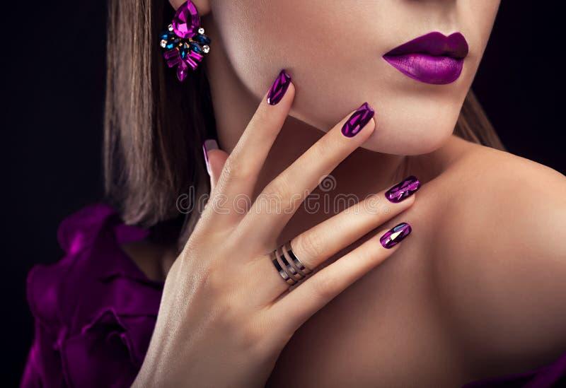 Mujer hermosa con joyería que lleva perfecta del maquillaje y de la manicura imagen de archivo