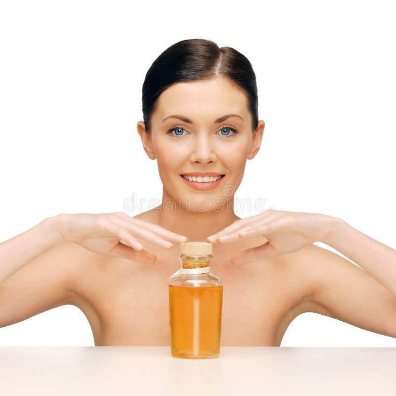 Mujer hermosa con la botella de aceite imagen de archivo
