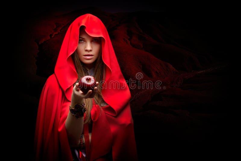 Mujer hermosa con la capa roja que sostiene la manzana fotografía de archivo libre de regalías