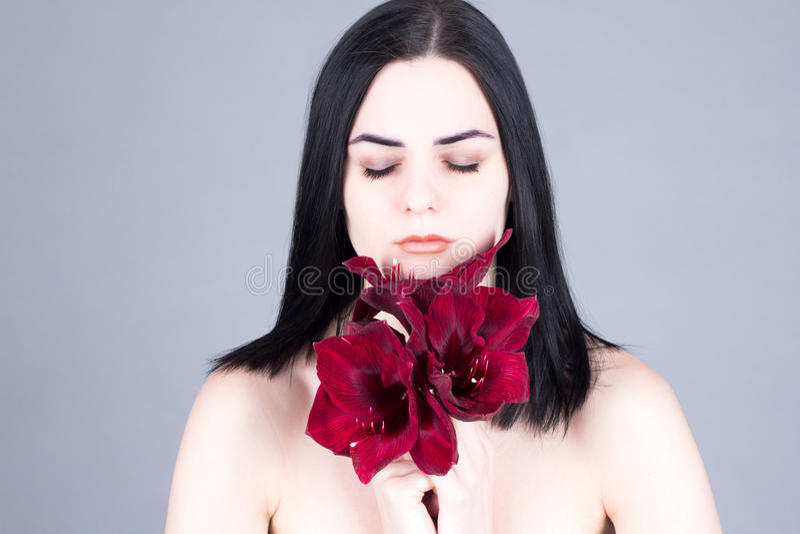 Mujer hermosa con la cara limpia y con las flores rojas en manos foto de archivo