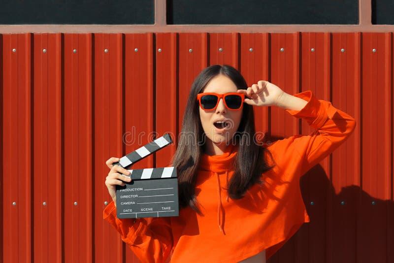 Mujer hermosa con la chapaleta del cine en fondo rojo imágenes de archivo libres de regalías