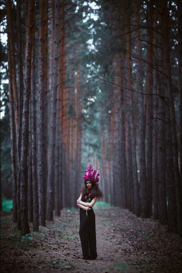Mujer hermosa con la corona que sostiene peonías púrpuras imagen de archivo libre de regalías