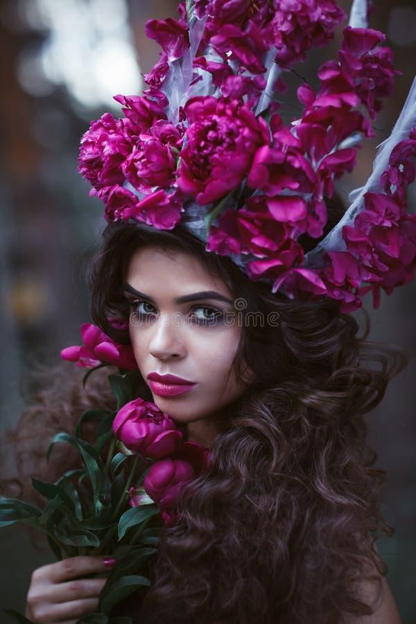 Mujer hermosa con la corona que sostiene peonías púrpuras fotos de archivo