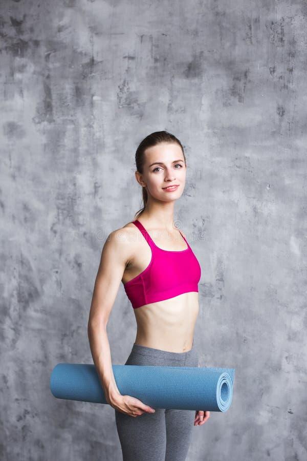 Mujer hermosa con la estera de la yoga dentro imagen de archivo