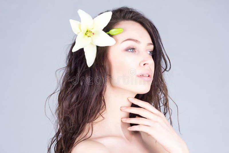 Mujer hermosa con la flor en el pelo rizado que toca su cuello Belleza, facial, BALNEARIO fotos de archivo