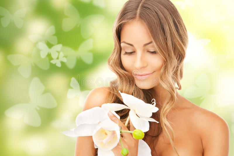 Mujer hermosa con la flor y las mariposas de la orquídea fotos de archivo libres de regalías