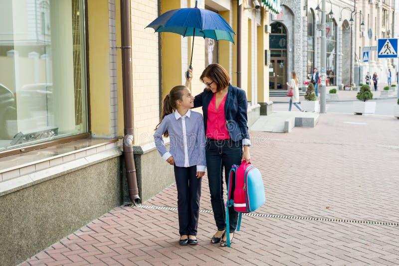 Mujer hermosa con la hija que camina junto a la escuela debajo de a fotografía de archivo