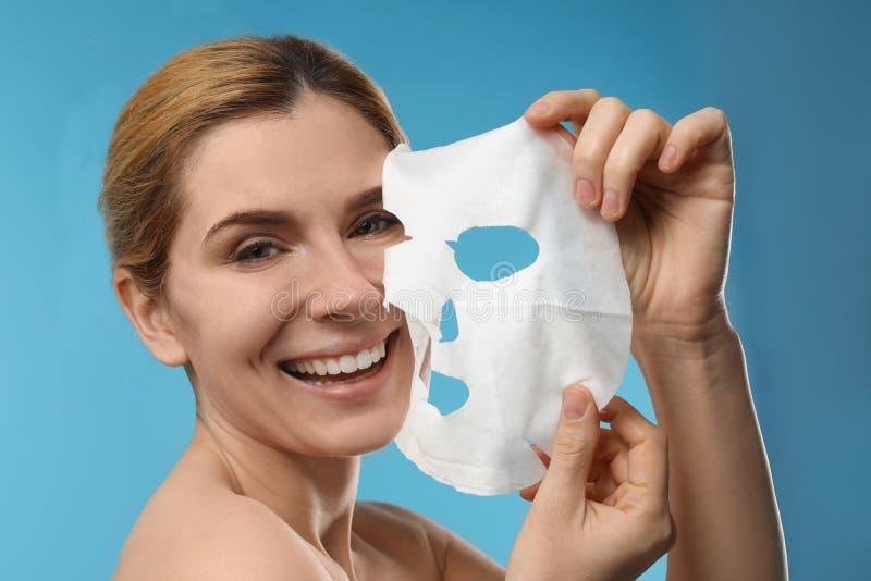 Mujer hermosa con la hoja facial de la máscara del algodón imagenes de archivo