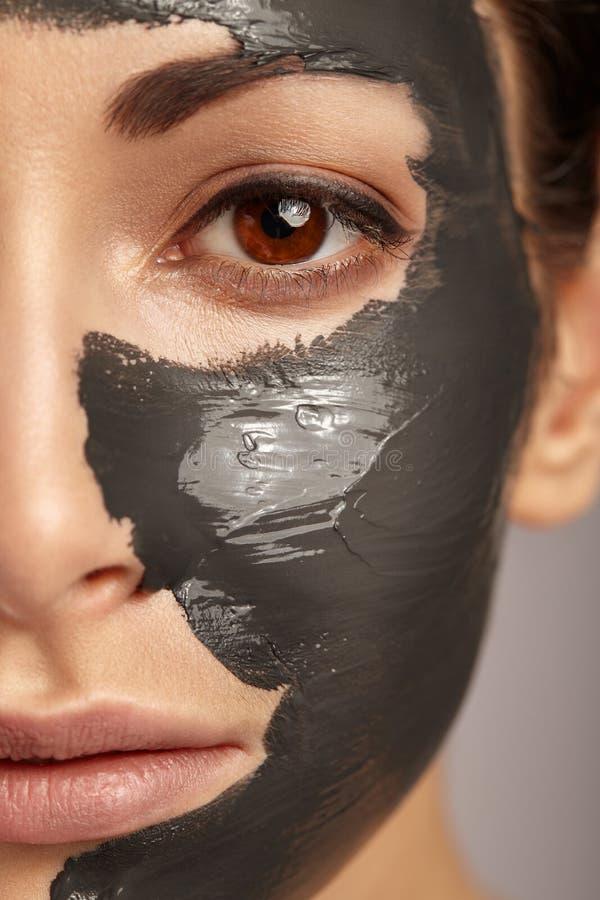 Mujer hermosa con la máscara facial imagen de archivo