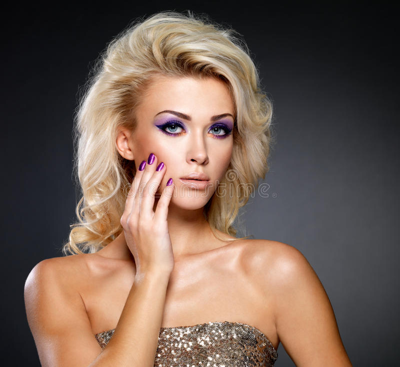 Mujer hermosa con la manicura de la belleza y el maquillaje púrpuras de ojos. fotografía de archivo