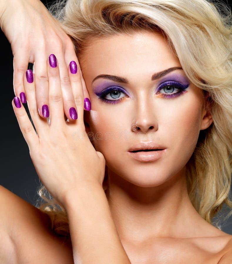 Mujer hermosa con la manicura de la belleza y el maquillaje púrpuras de ojos. fotos de archivo