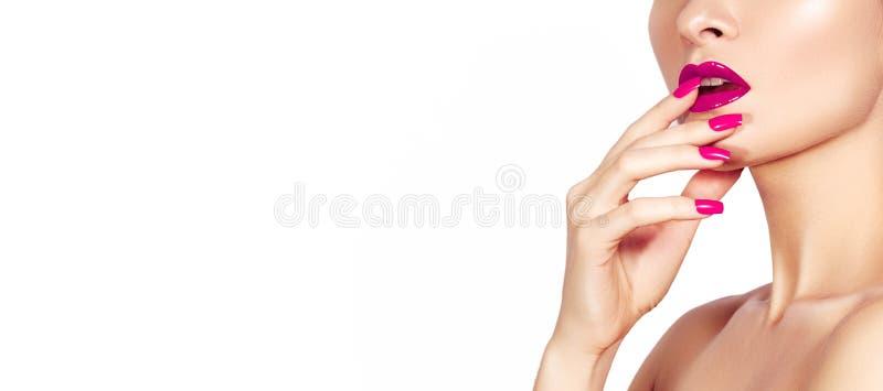 Mujer hermosa con la manicura roja de los clavos de la moda y los labios brillantes del maquillaje Esmalte de uñas de la moda con fotografía de archivo