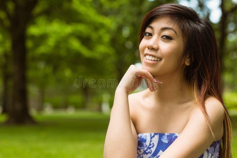 Mujer hermosa con la mano en la barbilla en parque fotografía de archivo
