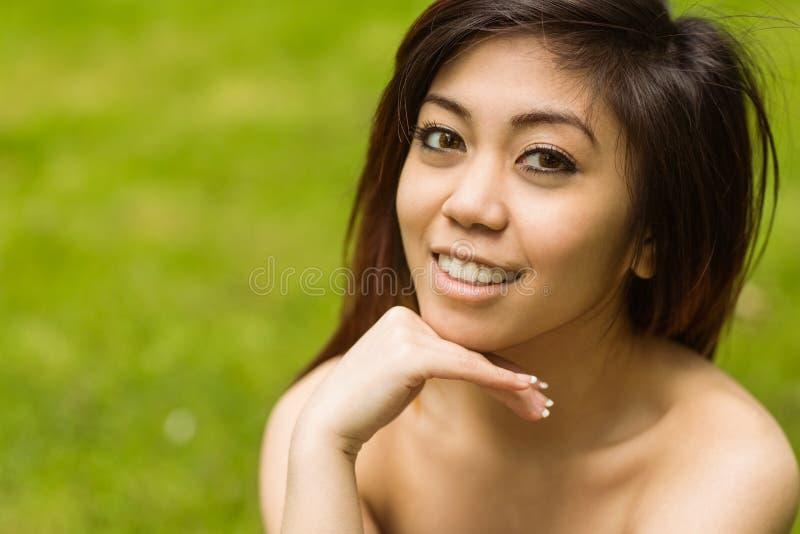 Mujer hermosa con la mano en la barbilla en parque imagen de archivo libre de regalías
