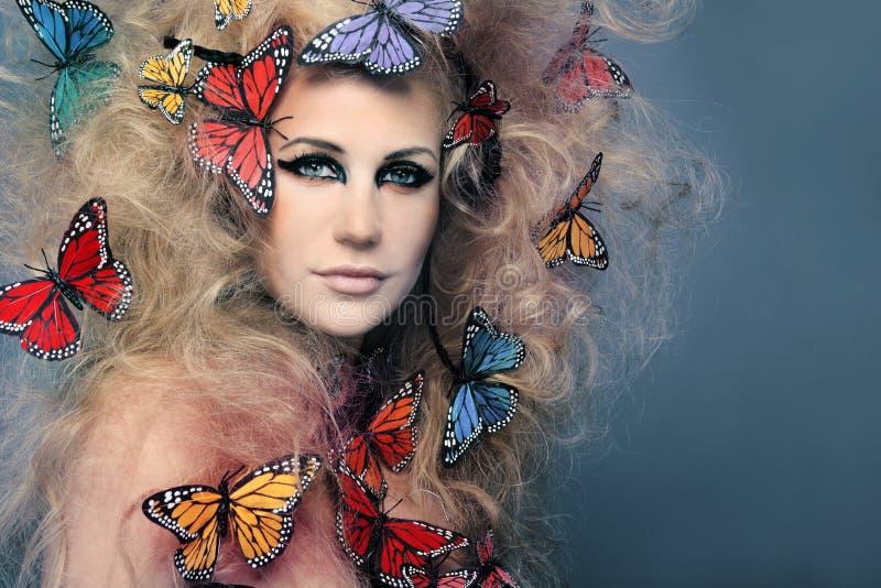 Mujer hermosa con la mariposa en pelo rizado grande. foto de archivo