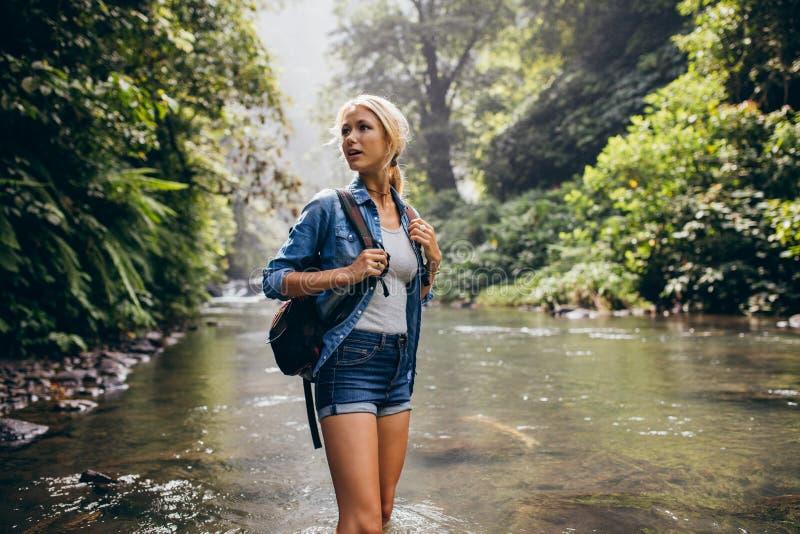 Mujer hermosa con la mochila que hace una pausa The Creek fotos de archivo