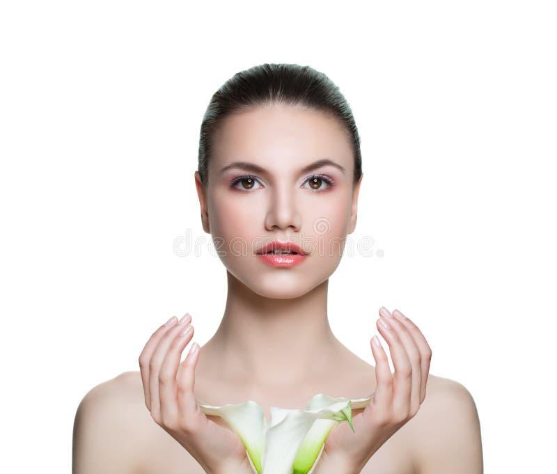 Mujer hermosa con la piel clara y flores aisladas en blanco Skincare y concepto facial del tratamiento foto de archivo libre de regalías