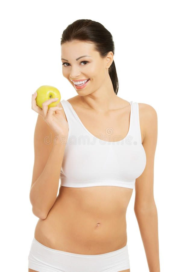 Mujer hermosa con la piel sana fresca limpia que lleva a cabo el appl verde imagen de archivo