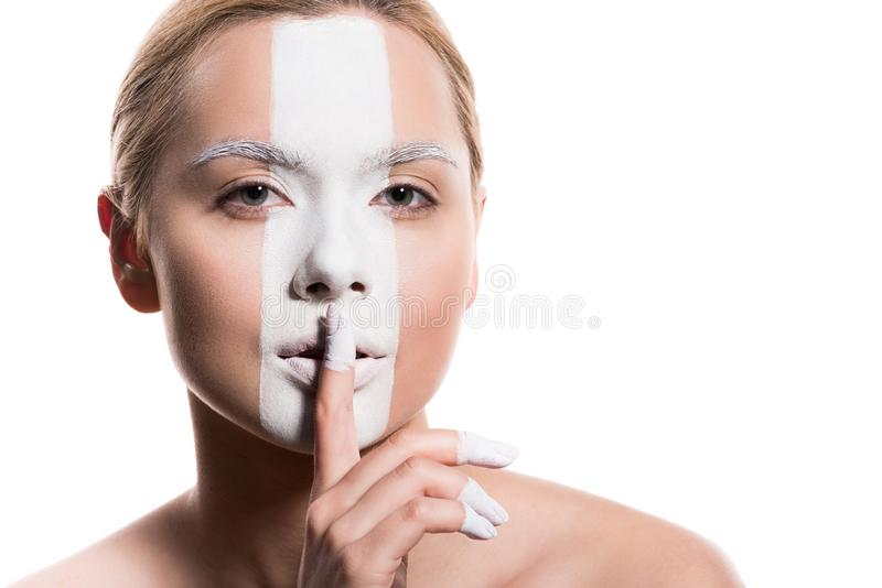mujer hermosa con la pintura blanca en la cara que muestra la muestra del silencio fotografía de archivo libre de regalías