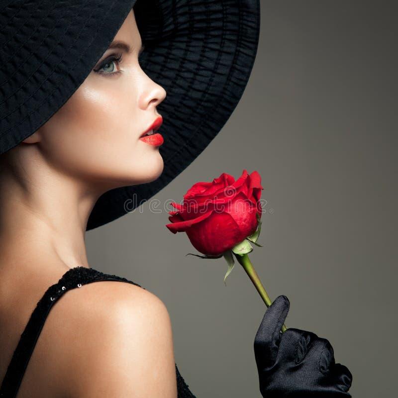 Mujer hermosa con la rosa del rojo Imagen retra de la moda foto de archivo