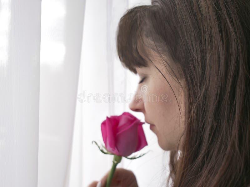 Mujer hermosa con la rosa rosada cerca de la ventana foto de archivo