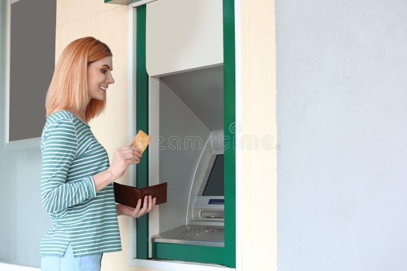 Mujer hermosa con la tarjeta de crédito cerca del cajero automático al aire libre imagenes de archivo