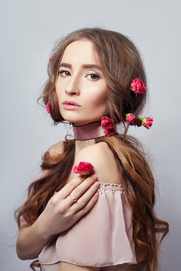 Mujer hermosa con las flores color de rosa en su pelo largo, un vendaje alrededor de su cuello Piel hermosa limpia de la cara, co imagen de archivo libre de regalías