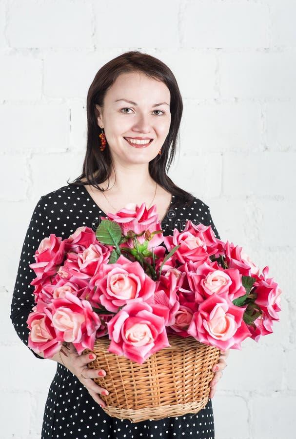 Mujer hermosa con las flores rojas en la cesta fotografía de archivo libre de regalías