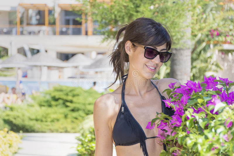 Mujer hermosa con las lentes de sol negros y el traje de baño imágenes de archivo libres de regalías