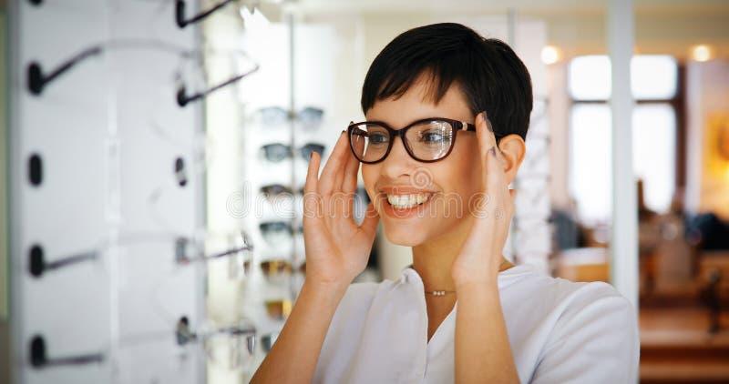 Mujer hermosa con las lentes que intentan del óptico foto de archivo