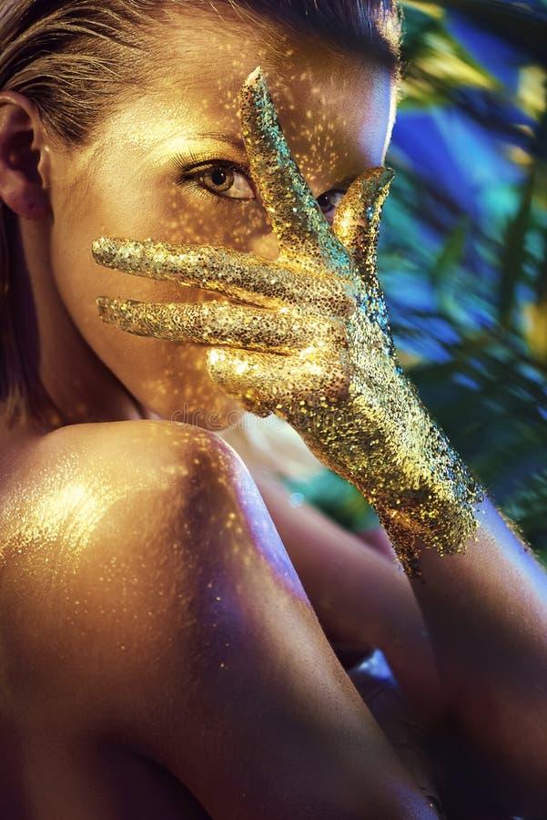 Mujer hermosa con las manos del oro que brillan imagen de archivo libre de regalías
