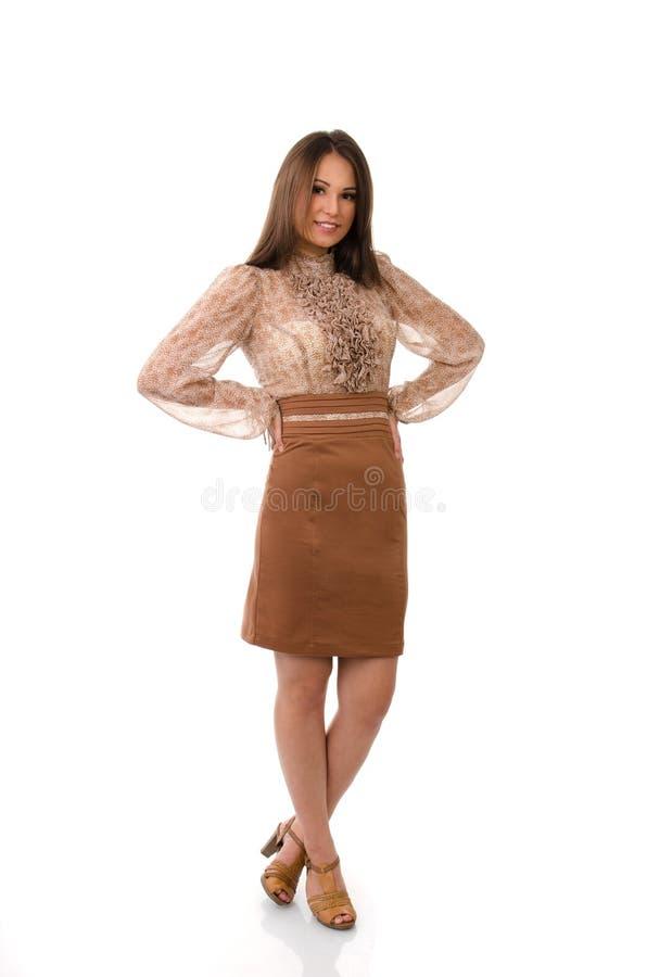 Mujer hermosa con las manos en la cintura y las piernas cruzadas fotos de archivo