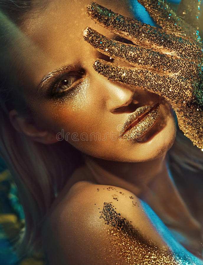 Mujer hermosa con las manos y los labios de oro que brillan fotografía de archivo libre de regalías