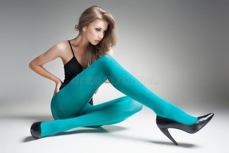 Mujer hermosa con las piernas atractivas largas en medias y tacones altos imagen de archivo