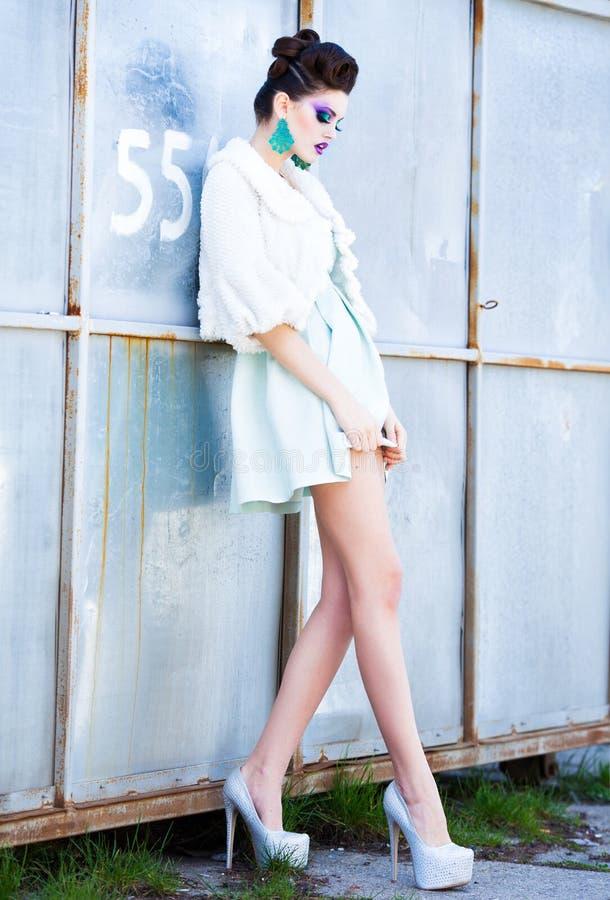 Mujer hermosa con las piernas largas en la presentación blanca del vestido, de la piel y de los tacones altos al aire libre imagenes de archivo