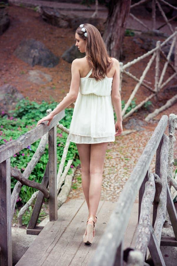 Mujer hermosa con las piernas largas que llevan el vestido blanco que camina en el puente en el bosque imagenes de archivo