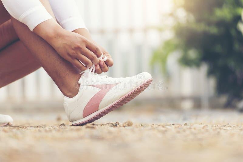 Mujer hermosa con las zapatillas deportivas con luz del sol por la mañana foto de archivo