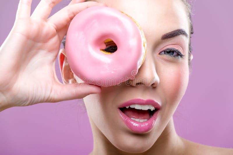 Mujer hermosa con los anillos de espuma, un ojo que un buñuelo rosado foto de archivo libre de regalías