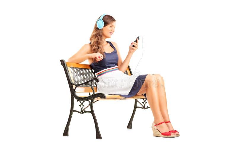 Mujer hermosa con los auriculares que se sientan en banco imagenes de archivo