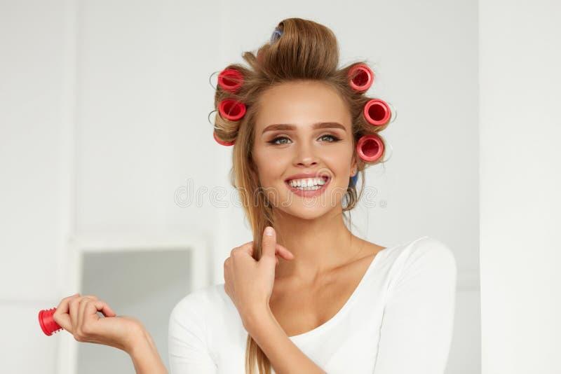 Mujer hermosa con los bigudíes de pelo, rodillos del pelo en rizado sano fotos de archivo