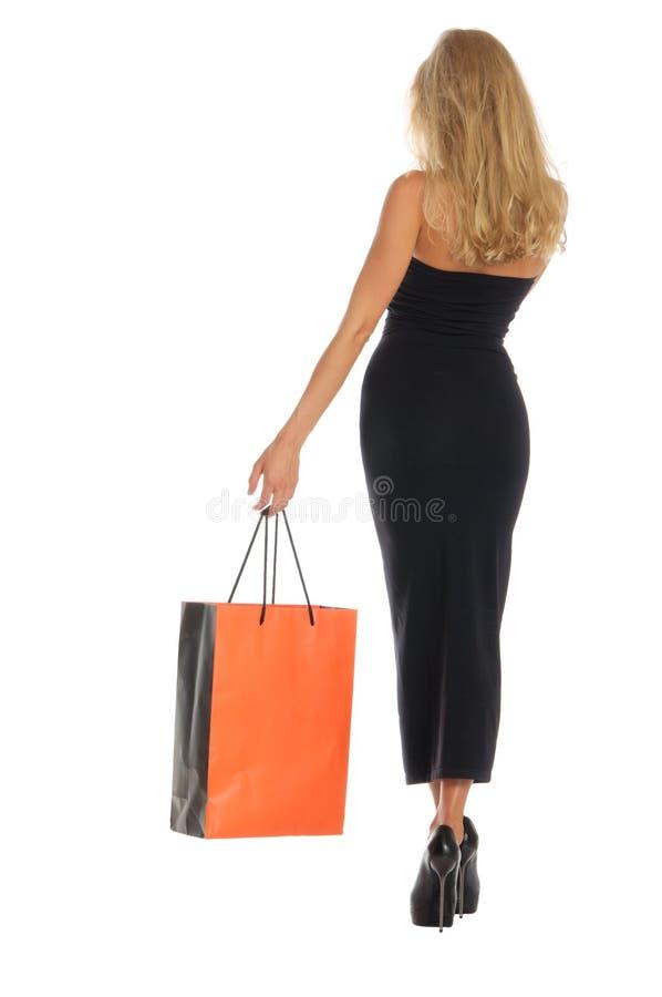 Mujer hermosa con los bolsos de compras anaranjados fotos de archivo libres de regalías