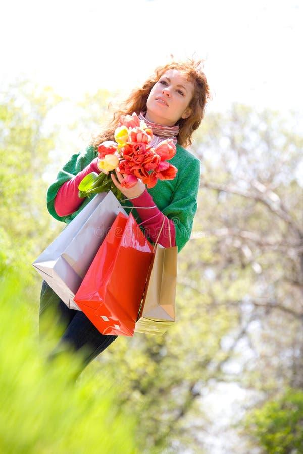 Mujer hermosa con los bolsos y los tulipanes de compras imagen de archivo