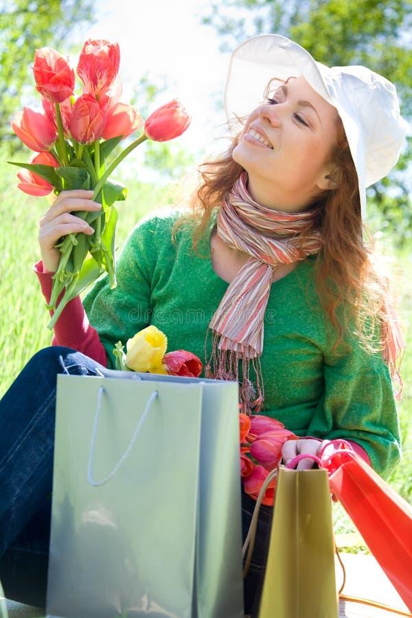 Mujer hermosa con los bolsos y los tulipanes de compras imagen de archivo libre de regalías