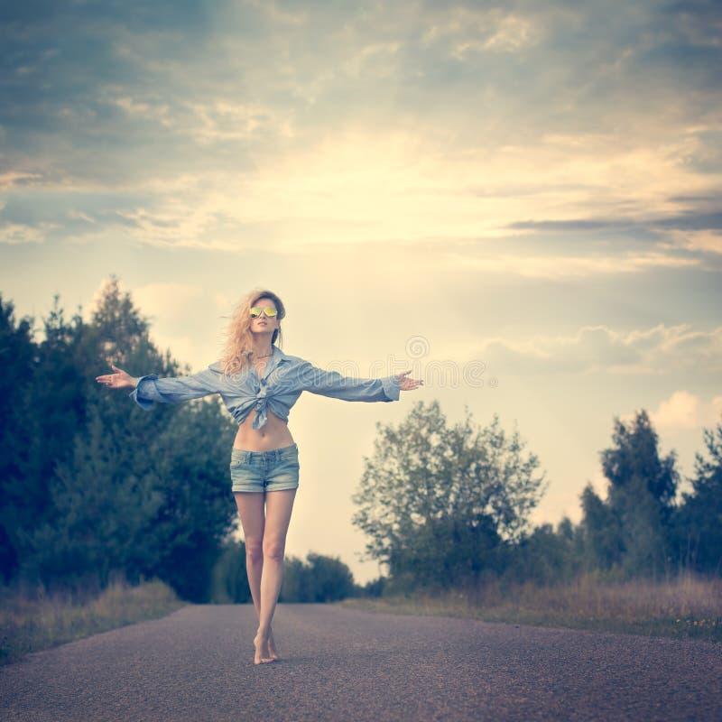 Mujer hermosa con los brazos abiertos bajo salida del sol foto de archivo libre de regalías