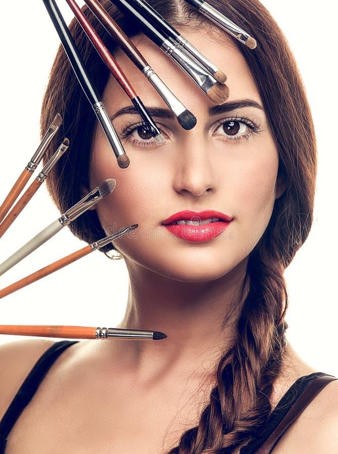 Mujer hermosa con los cepillos del maquillaje imagen de archivo libre de regalías